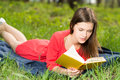 Beautiful young girl reads book in park at summer day Royalty Free Stock Photography