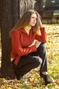 Beautiful young girl in red jacket is sitting near a tree Royalty Free Stock Images