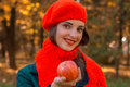 Beautiful young girl in a red scarf and hat smiling  holding an Apple in his hand, close-up Royalty Free Stock Photo