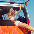 A beautiful young girl in retro look with a white swimsuit a ba bandana sunglasses and flip flops is sitting the car trunk Stock Photo