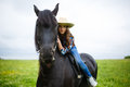 Beautiful young girl riding a horse in countryside Royalty Free Stock Photo