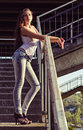 Beautiful young girl in shirt and jeans stands on stairs at sunset time Royalty Free Stock Photo
