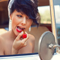 A beautiful young girl with short hair cut and blue eyes is looking into the side view mirror is putting on red lipstick Stock Images