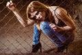 Beautiful young girl sitting behind metallic lattice Royalty Free Stock Photo