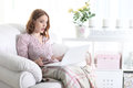 Beautiful young girl sitting in a chair with a laptop Royalty Free Stock Photo