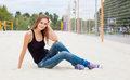 Beautiful young girl sitting on the sand nex to the net for volleyball of Sunny warm day Royalty Free Stock Photo