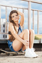 Beautiful young girl sitting on skateboard in day Royaltyfri Bild
