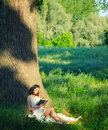 Beautiful young girl sitting under giant oak and reading book in spring