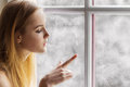 Beautiful young girl sitting by the window winter day and draws the sun on the frozen window Royalty Free Stock Photo