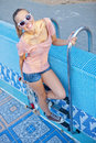 A beautiful young girl with a skateboard on the pool ladder Stock Image