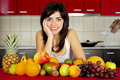 Beautiful young girl smiling sitting at a the table full of fresh fruits Stock Photo