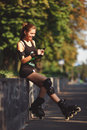 Beautiful young girl sporting appearance rollerblading sitting and talking on a cell phone cheerful on roller skates in the Royalty Free Stock Photo