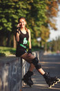 Beautiful young girl sporting appearance rollerblading sitting and talking on a cell phone cheerful on roller skates in the Stock Images