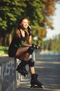 Beautiful young girl sporting appearance rollerblading sitting and talking on a cell phone cheerful on roller skates in the Royalty Free Stock Photography