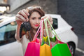 Beautiful young girl stands near a white car, makes a shopping Royalty Free Stock Photo