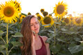 Beautiful young girl in sunflowers is a serious conversation on the phone at sunset Stock Images