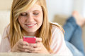Beautiful young girl texting on her cellphone lying sofa Royalty Free Stock Photo