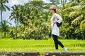 Beautiful young girl traveler in hat, glasses, with backpack walks along a rice field with green grass, palms, sky Bali Indonesia Royalty Free Stock Photo