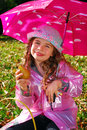Beautiful young girl with umbrella in raincoat in autumn garden Stock Photos