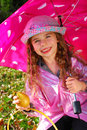 Beautiful young girl with umbrella in raincoat in autumn garden Stock Image
