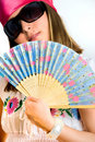 Beautiful young girl waving a fan Stock Photo