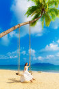 Beautiful young girl in a white dress sits on a swing under a pa palm tree tropical beach summer vacation Stock Photos