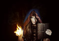 Beautiful young halloween witch old magical book fire wizard wearing vintage gothic dress with hood holding of spells in leather Royalty Free Stock Photos