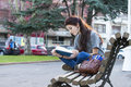 Beautiful young happiness girl sitting on bench and reading book hipster old wood in the street Stock Image