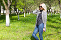 Beautiful young happy blonde girl in coat, jeans and sunglasses walking in the Park on a Sunny day