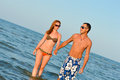 Beautiful young happy couple walking holding hands on seashore smiling in swimsuite summer outdoors Stock Images