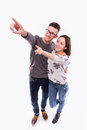 Beautiful young happy hipster couple love smiling embracing point finger to empty copy space Royalty Free Stock Photo
