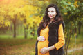 Beautiful young happy pregnant woman staying in fashion clothes in autumn park touching her belly and smiling. Royalty Free Stock Photo