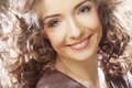 Beautiful young happy smiling woman close up portrait of curly Stock Image