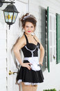 Beautiful young housemaid stands near front door of house white country and smiles Stock Image