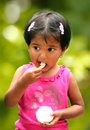 Beautiful young indian girl child enjoying ice cre cream in a park the photo shows female kid in pink dress smiling and relishing Stock Photo