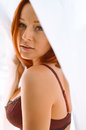 Beautiful young lady with ginger hair in dark red picture of bra black lace sexy girl looking at camera on blurred white Royalty Free Stock Image