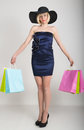 Beautiful young lady in a little blue dress on high heels, holding colorful bags. Girl goes shopping Royalty Free Stock Photo