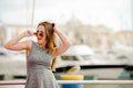 Beautiful young lady in sunglasses wearing dress portrait of standing beside railing charming girl grey on blurred embankment Royalty Free Stock Image