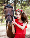 Beautiful young lady wearing red dress riding a horse at sunny summer day. Brunette with long curly hair with flowers on her head Royalty Free Stock Photo