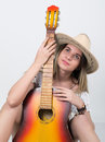 Beautiful young leggy blond Country girl in a litl white dress and cowboy hat with a guitar Royalty Free Stock Photo