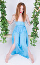 Beautiful young leggy redhaired woman in a long blue dress on a swing wooden swing suspended from a rope hemp rope wrapped vine Royalty Free Stock Images