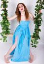Beautiful young leggy redhaired woman in a long blue dress on a swing wooden swing suspended from a rope hemp rope wrapped vine Royalty Free Stock Photos