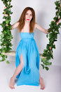Beautiful young leggy redhaired woman in a long blue dress on a swing wooden swing suspended from a rope hemp rope wrapped vine Stock Photos