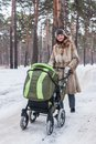Beautiful young mother with carriage happy walking baby in park Stock Photography