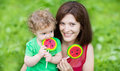 Beautiful young mother and her baby daughter eating candy funny Royalty Free Stock Photos