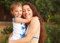 Beautiful young mother hugging her small kid girl with happy smile and closed eyes Royalty Free Stock Photo
