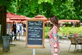 Beautiful young parisian woman reading menu handwritten in restaurant in the tuileries garden on a sunny summer day Stock Photo