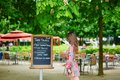 Beautiful young parisian woman reading menu handwritten in restaurant in the tuileries garden on a sunny summer day Royalty Free Stock Photography