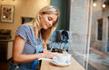 Beautiful young pregnant girl sitting in cafe reading magazine a Royalty Free Stock Photo