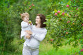 Beautiful young pregnant woman and her laughing baby daughter women pick apples Stock Photos